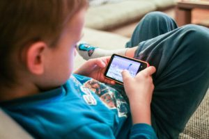Little boy playing video games on his phone - discussing the scary stuff with your child